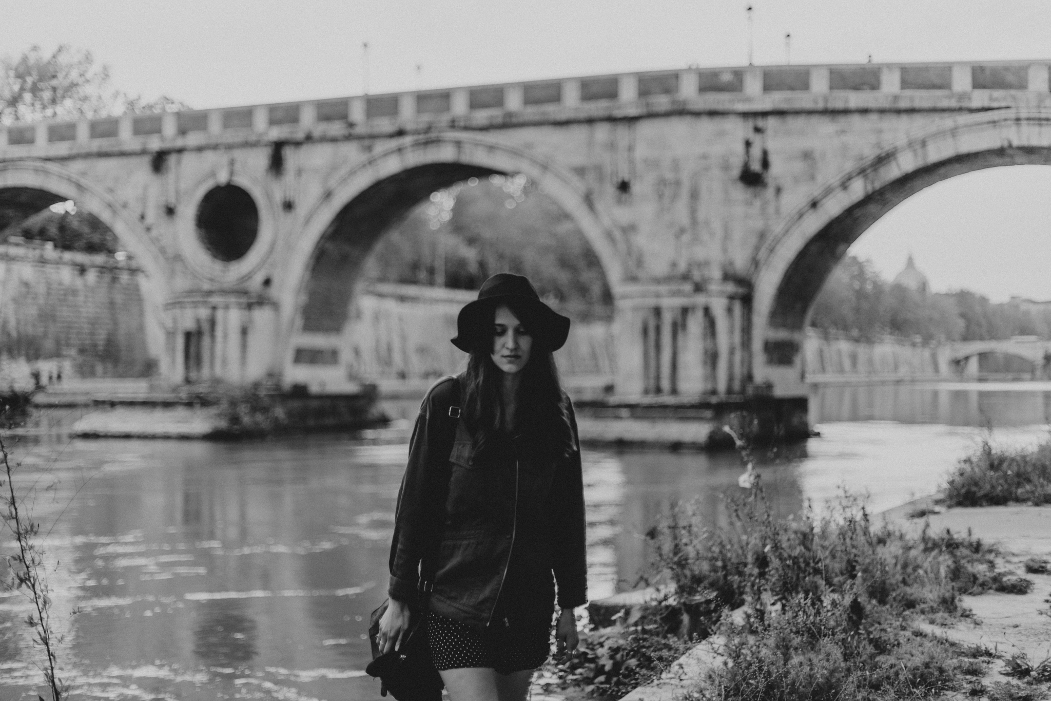 black and white photograph of woman in trastevere under bridge on tiber river