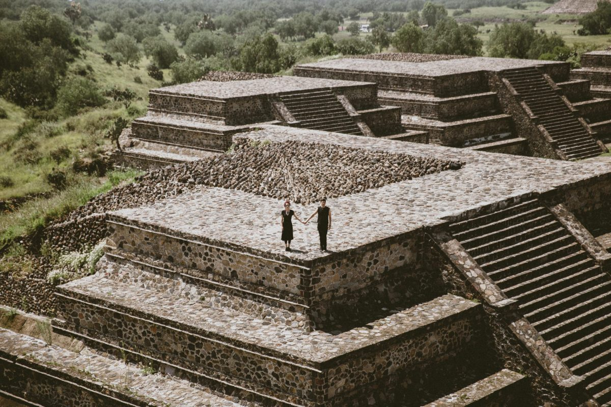 holding hands on top of teotihuacan pyramid in mexico
