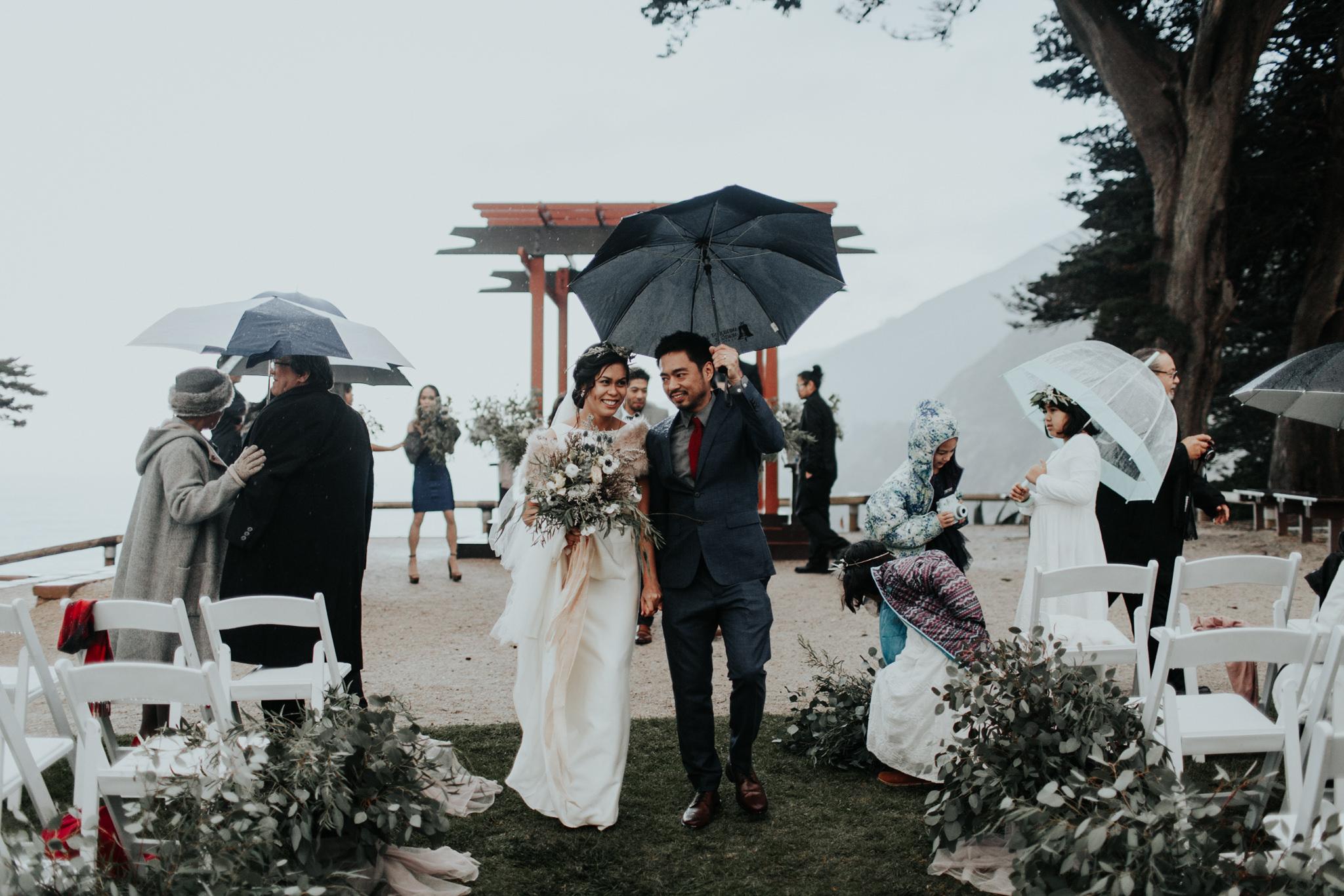 ragged point inn wedding during rain winter coastal wedding umbrellas