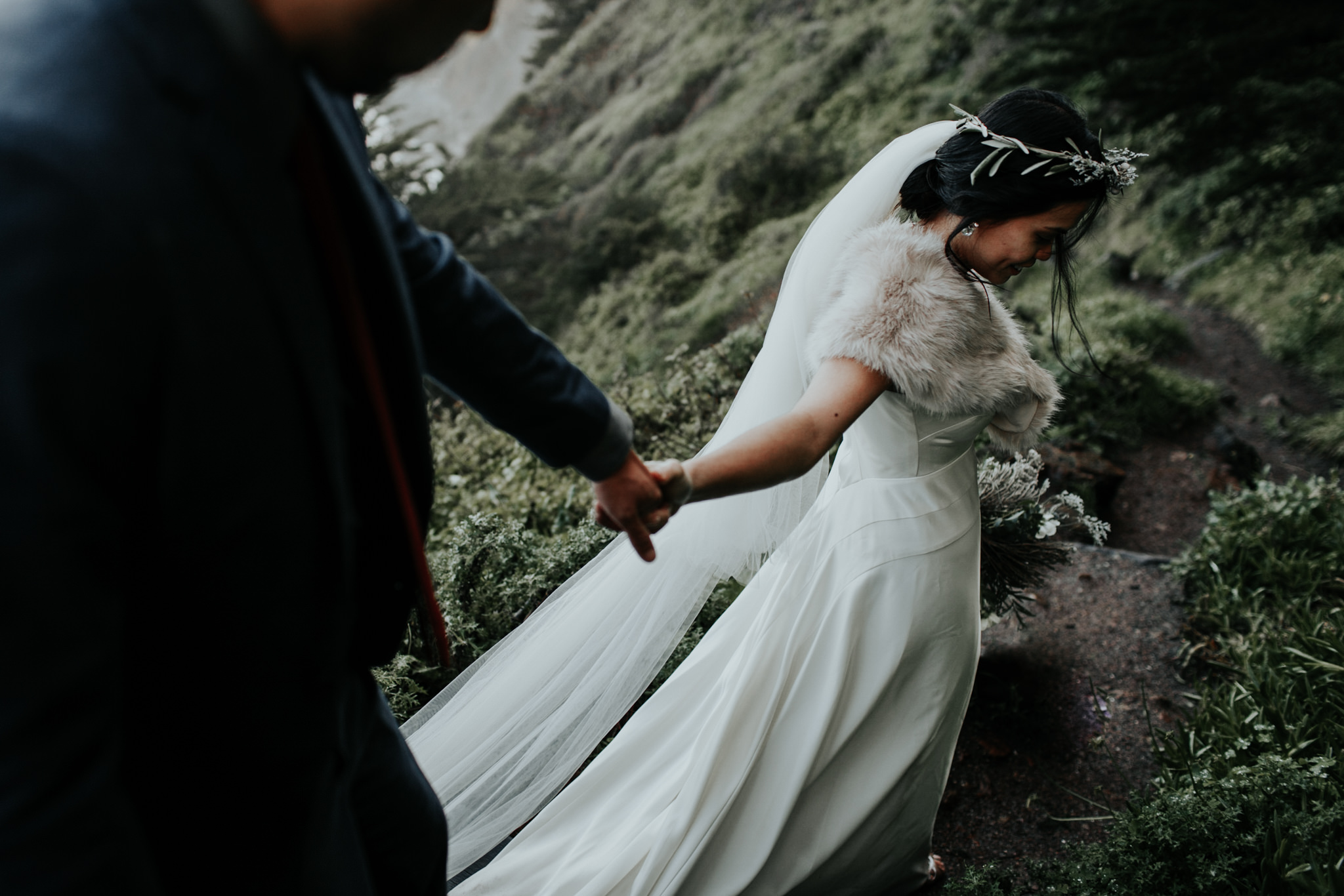 hiking romantics coastal bride and groom winter wedding big sur coast ragged point inn bride and groom walking and holding hands greenery moody